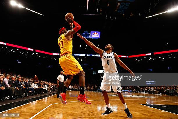 LeBron James of the Cleveland Cavaliers shoots the ball against Alan Anderson of the Brooklyn Nets during their game at Barclays Center on December 8...
