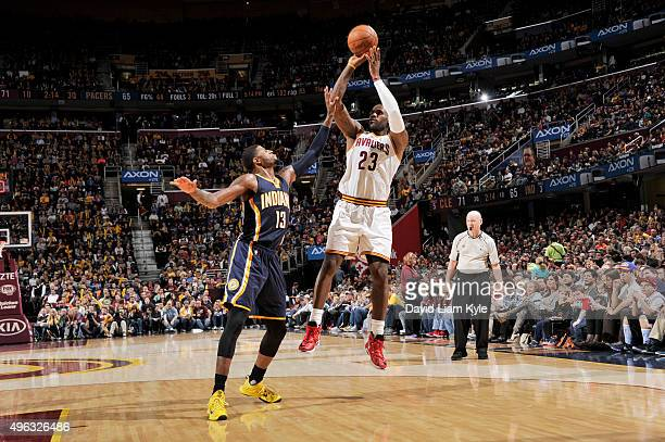 LeBron James of the Cleveland Cavaliers shoots the ball against Paul George of the Indiana Pacers on November 8 2015 at Quicken Loans Arena in...