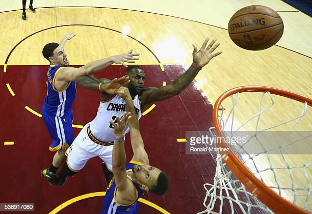 LeBron James of the Cleveland Cavaliers shoots the ball during the second half against Klay Thompson of the Golden State Warriors and Stephen Curry...