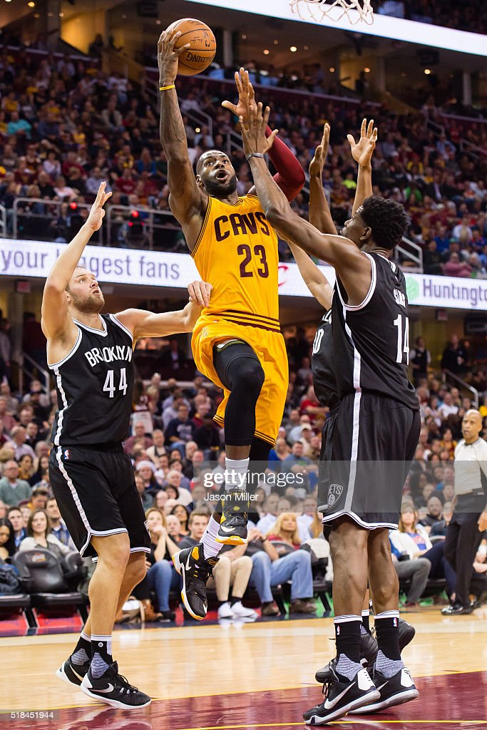 LeBron James #23 of the Cleveland Cavaliers shots over Bojan Bogdanovic #44 and Henry Sims #14 of the Brooklyn Nets during the first half at Quicken Loans Arena on March 31, 2016 in Cleveland, Ohio.