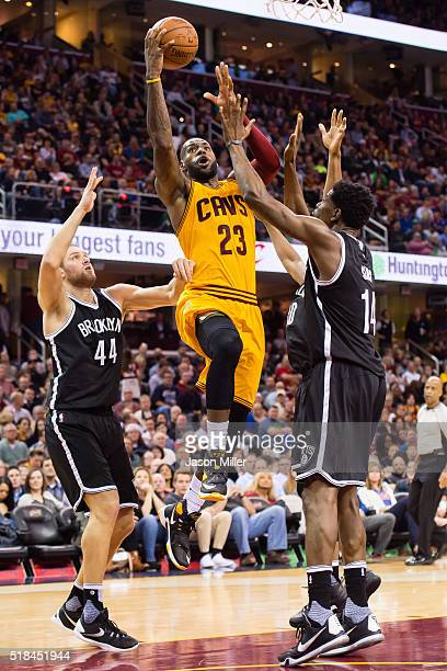 LeBron James of the Cleveland Cavaliers shots over Bojan Bogdanovic and Henry Sims of the Brooklyn Nets during the first half at Quicken Loans Arena...