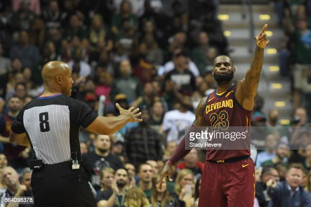 LeBron James of the Cleveland Cavaliers signals a call along with referee Marc Davis during the second half of a game against the Milwaukee Bucks at...