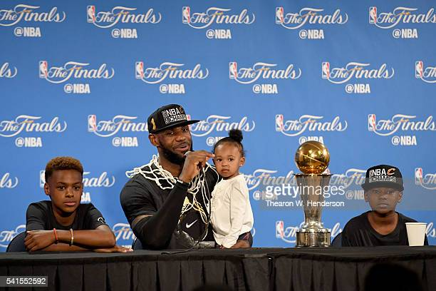 LeBron James of the Cleveland Cavaliers sits with his children LeBron Jr Zhuri and Bryce during a press conference after defeating the Golden State...