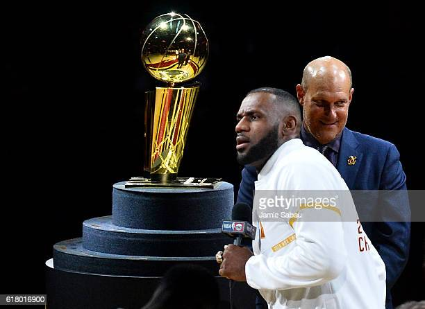 LeBron James of the Cleveland Cavaliers speaks in front of the Larry O'Brien Trophy after receiving his championship ring before the game against the...