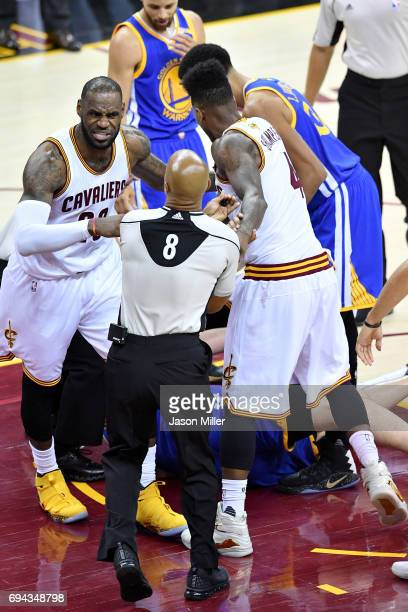 LeBron James of the Cleveland Cavaliers speaks to an official after Iman Shumpert of the Cleveland Cavaliers compete for the ball with Zaza Pachulia...