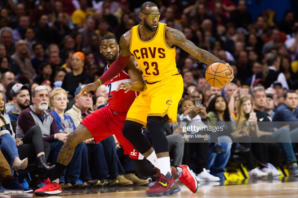 LeBron James #23 of the Cleveland Cavaliers spins away from John Wall #2 of the Washington Wizards during the first half at Quicken Loans Arena on March 25, 2017 in Cleveland, Ohio.