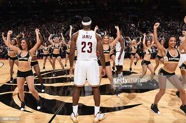 LeBron James of the Cleveland Cavaliers stands on the court while the Toronto Raptors dance team performs before the game against the Toronto Raptors...