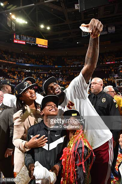LeBron James of the Cleveland Cavaliers takes a selfie with his family after winning game four against the Atlanta Hawks at the Quicken Loans Arena...