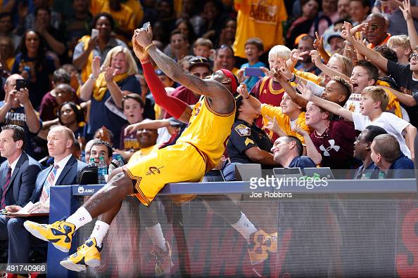 LeBron James of the Cleveland Cavaliers takes a selfie with young fans during a timeout in the second half of a preseason game against the Atlanta...