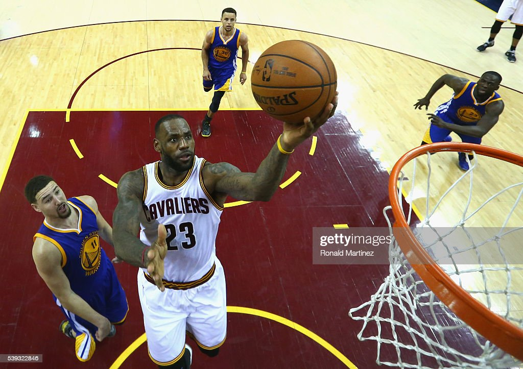 LeBron James of the Cleveland Cavaliers takes a shot in front of Klay Thompson Stephen Curry and Draymond Green of the Golden State Warriors in the...