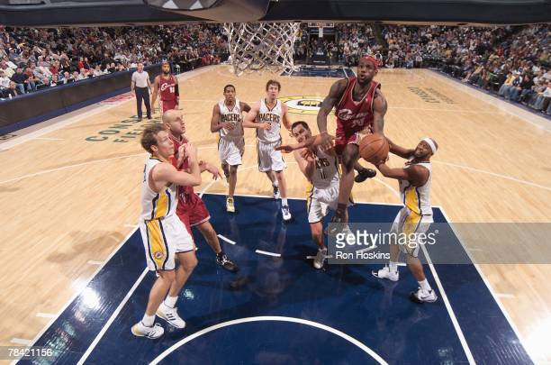 LeBron James of the Cleveland Cavaliers takes the ball to the basket against Jeff Foster and Jamaal Tinsley of the Indiana Pacers during the game at...