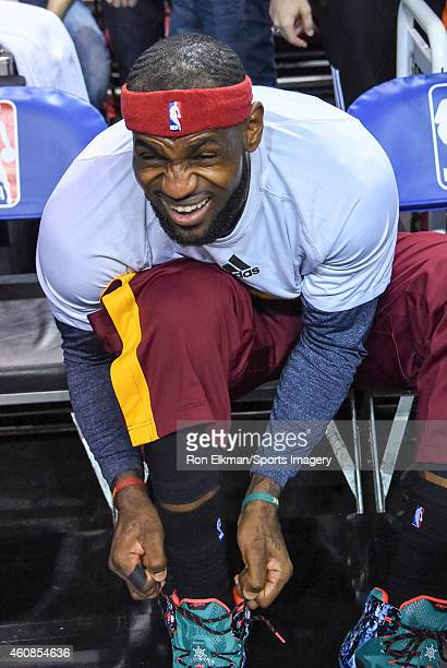 LeBron James of the Cleveland Cavaliers ties his shoes before a game against the Miami Heat at American Airlines Arena on December 25 2014 in Miami...