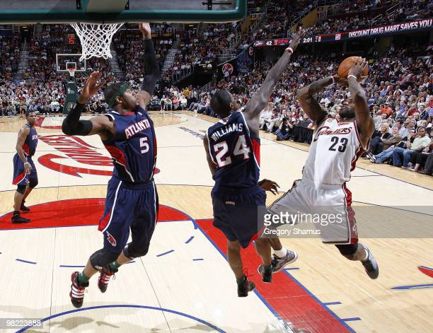 LeBron James of the Cleveland Cavaliers tries to get a shot off over Josh Smith and Marvin Williams of the Atlanta Hawks on April 2 2010 at the...