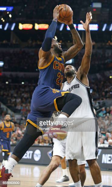 LeBron James of the Cleveland Cavaliers tries to score against Kawhi Leonard of the San Antonio Spurs but shot was blocked at ATT Center on March 27...