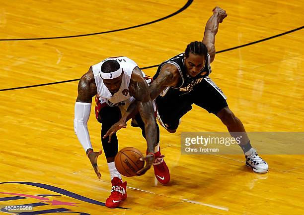 LeBron James of the Miami Heat and Kawhi Leonard of the San Antonio Spurs battle for a loose ball during Game Four of the 2014 NBA Finals at American...