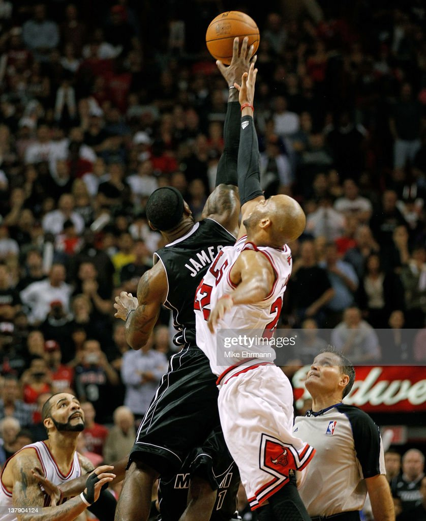 LeBron James #6 of the Miami Heat and Taj Gibson #22 of the Chicago Bulls go for a jump ball during a game at American Airlines Arena on January 29, 2012 in Miami, Florida.