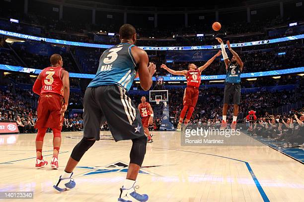 LeBron James of the Miami Heat and the Eastern Conference attempts a 3pt shot against Russell Westbrook of the Oklahoma City Thunder and the Western...