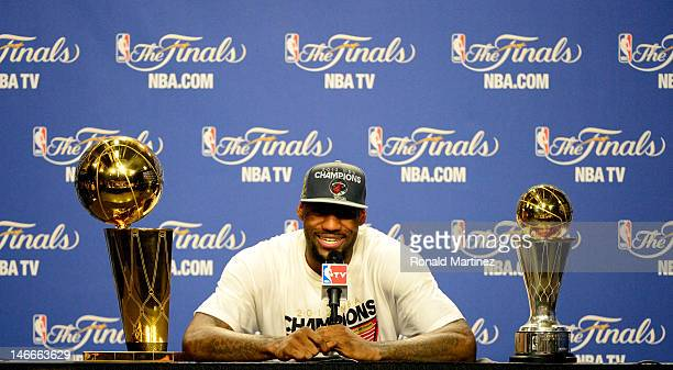LeBron James of the Miami Heat answers questions from the media next to the Larry O'Brien Finals Championship trophy and James' Bill Russell Finals...