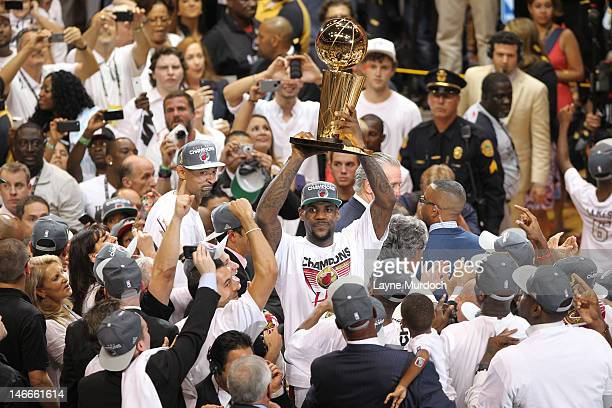 LeBron James of the Miami Heat celebrates while holding up the Larry O'Brien NBA Championship Trophy after his team wins the NBA Championship by...