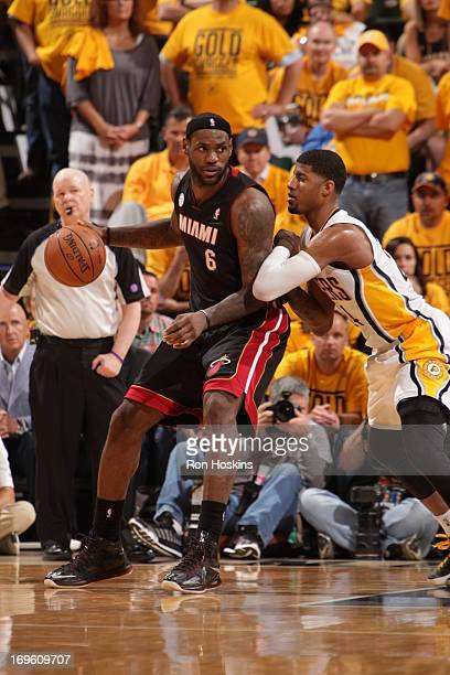 LeBron James of the Miami Heat controls the ball against Paul George of the Indiana Pacers in Game Four of the Eastern Conference Finals during the...