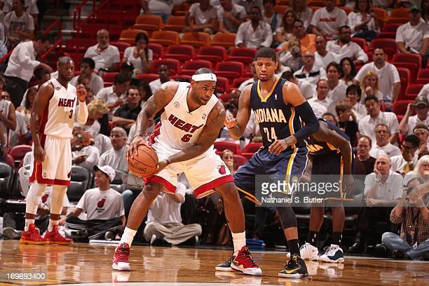 LeBron James of the Miami Heat controls the ball against Paul George of the Indiana Pacers in Game Five of the Eastern Conference Finals on May 30...