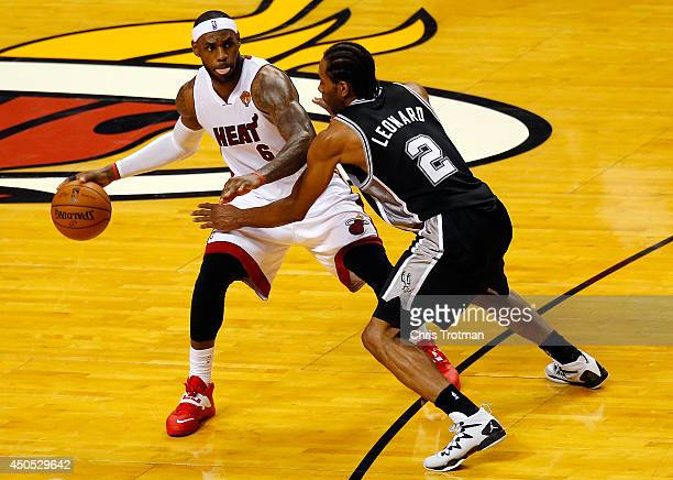 LeBron James of the Miami Heat controls the ball as Kawhi Leonard of the San Antonio Spurs defends during Game Four of the 2014 NBA Finals at...