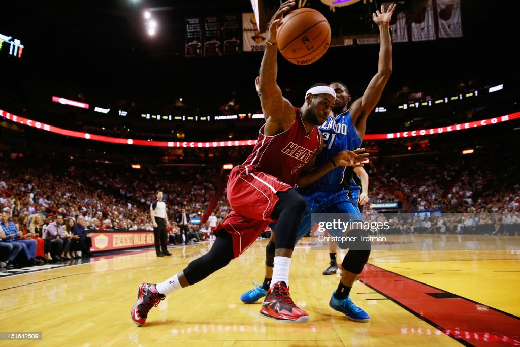 LeBron James #6 of the Miami Heat dribbles the ball under pressure from Maurice Harkless #21 of the Orlando Magic at American Airlines Arena on November 23, 2013 in Miami, Florida.