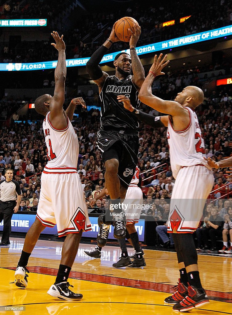 LeBron James #6 of the Miami Heat drives against Taj Gibson #22 and Ronnie Brewer #11 of the Chicago Bulls go for a jump ball during a game at American Airlines Arena on January 29, 2012 in Miami, Florida.