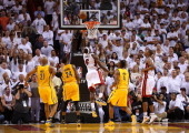 LeBron James of the Miami Heat drives and makes the game winning basket in overtime against the Indiana Pacers during Game One of the Eastern...