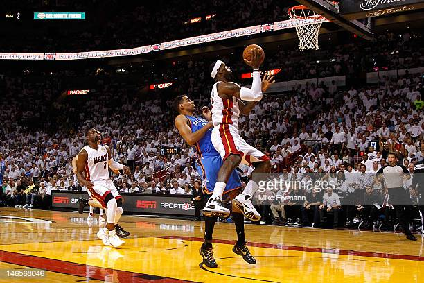 LeBron James of the Miami Heat drives for a shot attempt in the first quarter against Thabo Sefolosha of the Oklahoma City Thunder in Game Four of...