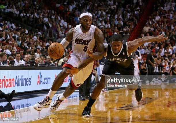 LeBron James of the Miami Heat drives on Joe Johnson of the Brooklyn Nets during a game at AmericanAirlines Arena on November 7 2012 in Miami Florida