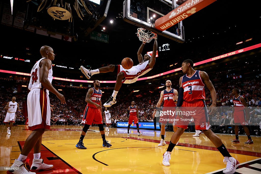 LeBron James #6 of the Miami Heat dunks the ball as Bradley Beal #3 of the Washington Wizards and Marcin Gortat #4 of the Washington Wizards look on at American Airlines Arena on November 3, 2013 in Miami, Florida.