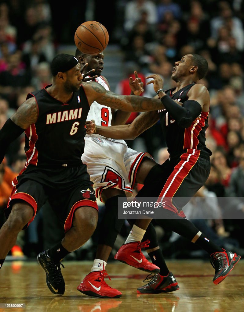 LeBron James of the Miami Heat fouls Loul Deng of the Chicago Bulls as Mario Chalmers defends at the United Center on December 5 2013 in Chicago...