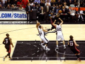 LeBron James of the Miami Heat goes up for a shot against Manu Ginobili of the San Antonio Spurs in the first half during Game Four of the 2013 NBA...