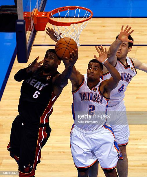LeBron James of the Miami Heat goes up for a shot against Nick Collison and Thabo Sefolosha of the Oklahoma City Thunder in the first quarter in Game...