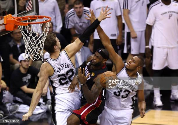 LeBron James of the Miami Heat goes up for a shot against Tiago Splitter and Boris Diaw of the San Antonio Spurs in the second half during Game Five...