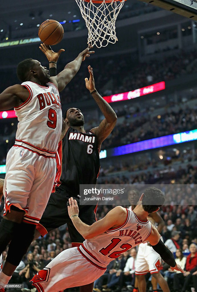 <a gi-track='captionPersonalityLinkClicked' href=/galleries/search?phrase=LeBron+James&family=editorial&specificpeople=201474 ng-click='$event.stopPropagation()'>LeBron James</a> #6 of the Miami Heat goes up for a shot over <a gi-track='captionPersonalityLinkClicked' href=/galleries/search?phrase=Kirk+Hinrich&family=editorial&specificpeople=201629 ng-click='$event.stopPropagation()'>Kirk Hinrich</a> #12 and Loul Deng #9 of the Chicago Bulls at the United Center on December 5, 2013 in Chicago, Illinois.