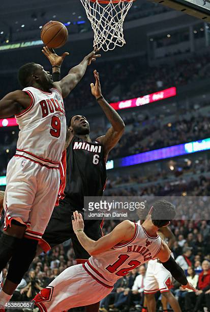 LeBron James of the Miami Heat goes up for a shot over Kirk Hinrich and Loul Deng of the Chicago Bulls at the United Center on December 5 2013 in...