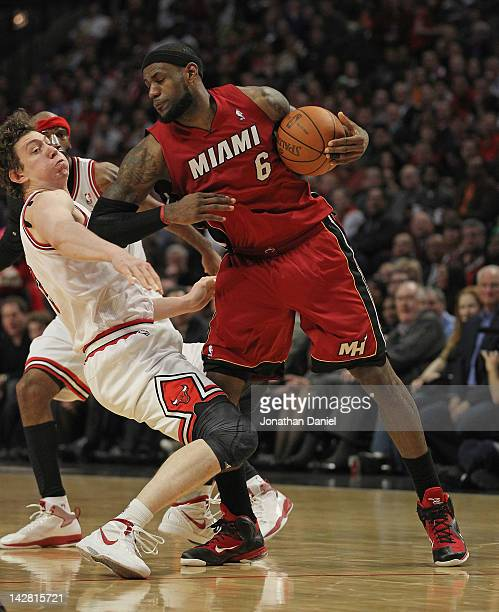 LeBron James of the Miami Heat hits Omer Asik of the Chicago Bulls in the chest with his elbow at the United Center on April 12 2012 in Chicago...
