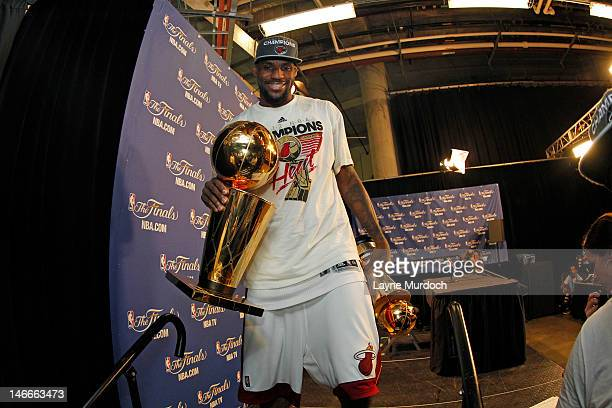 LeBron James of the Miami Heat holding both the Larry O'Brien NBA Championship Trophy and the Bill Russell Finals MVP Trophy after his team wins the...