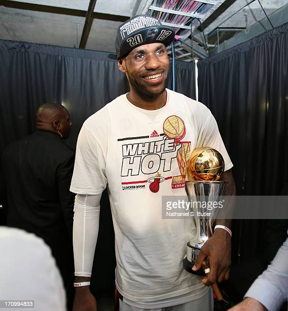 LeBron James of the Miami Heat holds the Bill Russell NBA Finals Most Valuable Player Award as he celebrates defeating the San Antonio Spurs in Game...