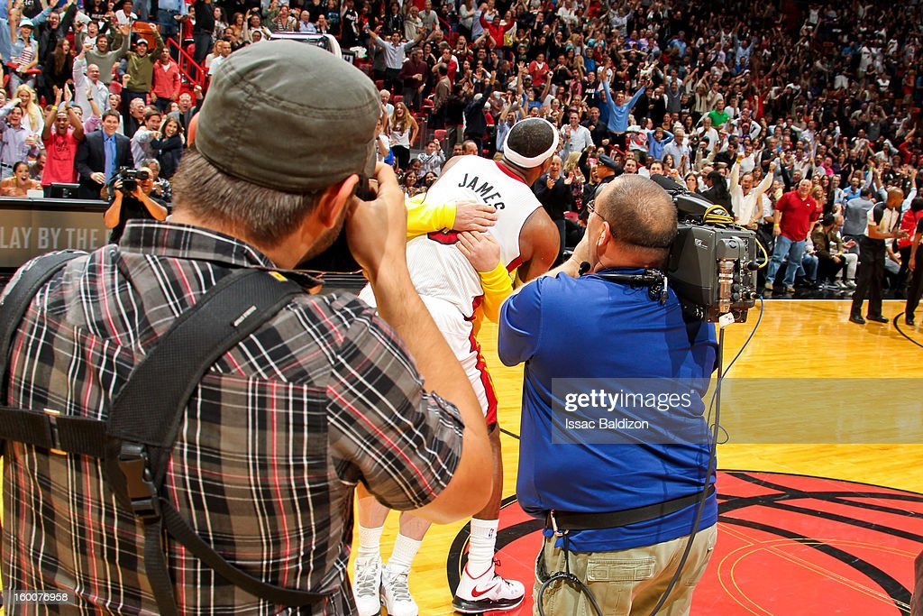 LeBron James #6 of the Miami Heat hugs fan Michael Drysch after Drysch made a half-court shot to win $75,000 for himself and $75,000 for the LeBron James Family Foundation Boys and Girls Club of America during halftime of a game against the Detroit Pistons on January 25, 2013 at American Airlines Arena in Miami, Florida.