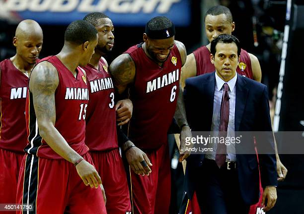 LeBron James of the Miami Heat is helped off the court after cramping up against the San Antonio Spurs during Game One of the 2014 NBA Finals at the...