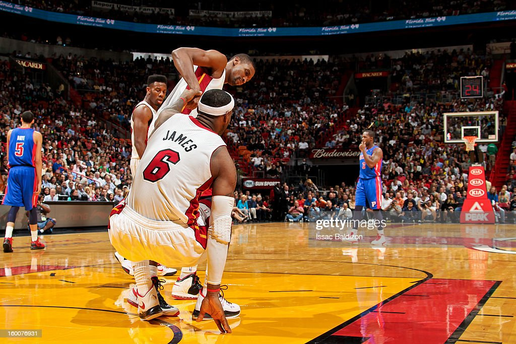 LeBron James #6 of the Miami Heat is helped up by teammate Chris Bosh #1 during a game against the Detroit Pistons on January 25, 2013 at American Airlines Arena in Miami, Florida.