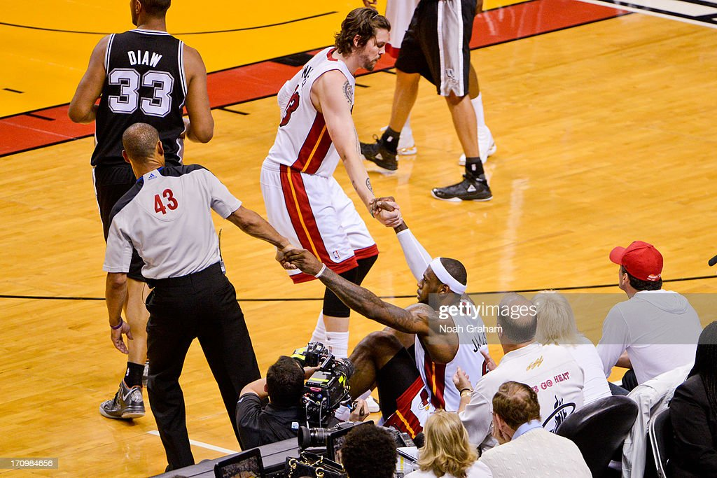 LeBron James #6 of the Miami Heat is helped up by teammate Mike Miller #13 and referee Dan Crawford #43 during Game Seven of the 2013 NBA Finals on June 20, 2013 at American Airlines Arena in Miami, Florida.
