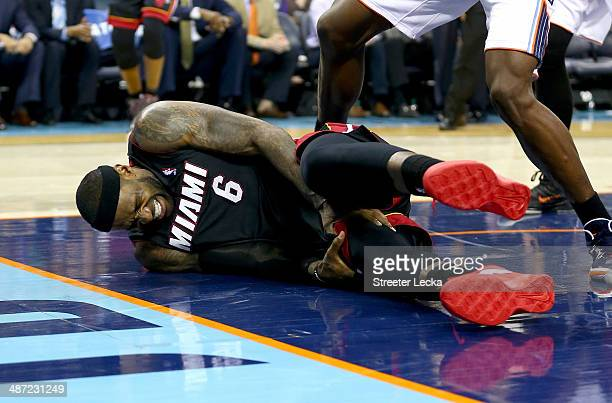 LeBron James of the Miami Heat is injured against the Charlotte Bobcats in Game Four of the Eastern Conference Quarterfinals during the 2014 NBA...