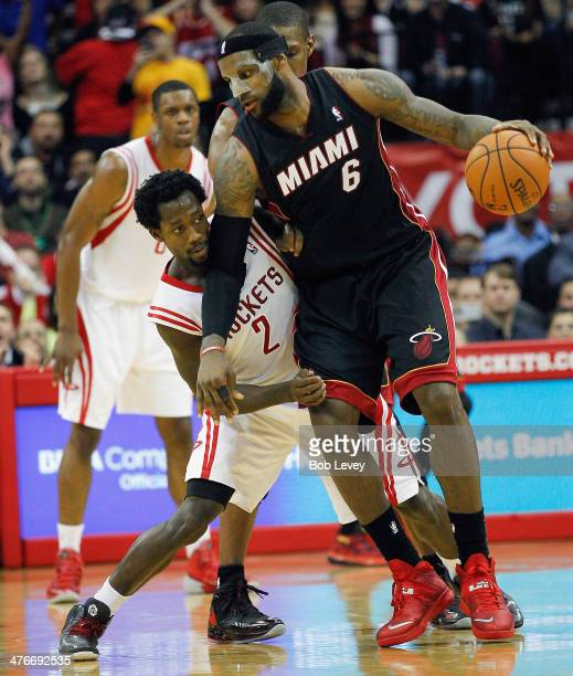 LeBron James of the Miami Heat looks to drive on Patrick Beverley of the Houston Rockets at Toyota Center on March 4 2014 in Houston Texas NOTE TO...