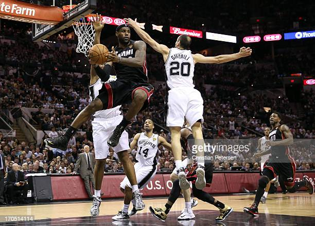LeBron James of the Miami Heat looks to pass around Manu Ginobili of the San Antonio Spurs in the fourth quarter during Game Four of the 2013 NBA...