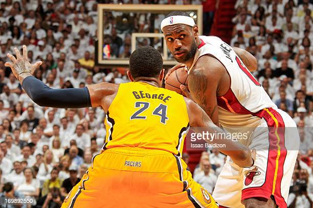 LeBron James of the Miami Heat looks to pass the ball against Paul George of the Indiana Pacers in Game Seven of the Eastern Conference Finals during...