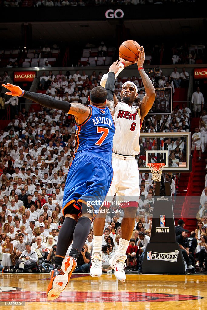 <a gi-track='captionPersonalityLinkClicked' href=/galleries/search?phrase=LeBron+James&family=editorial&specificpeople=201474 ng-click='$event.stopPropagation()'>LeBron James</a> #6 of the Miami Heat makes a three-point shot against <a gi-track='captionPersonalityLinkClicked' href=/galleries/search?phrase=Carmelo+Anthony&family=editorial&specificpeople=201494 ng-click='$event.stopPropagation()'>Carmelo Anthony</a> #7 of the New York Knicks in Game One of the Eastern Conference Quarterfinals during the 2012 NBA Playoffs on April 28, 2012 at American Airlines Arena in Miami, Florida.